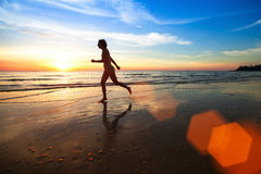 Young woman jogger at sunset on the seashore. Stock Photo