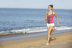 Young Woman Jogging Along Beach Royalty Free Stock Images