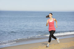 Young Woman Jogging Along Beach Stock Photography