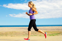 Young woman jogging along beach. Royalty Free Stock Images