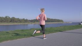 Woman jogging along a canal. Young woman jogging along a canal stock footage