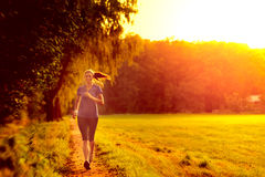 Young woman jogging along a country track Royalty Free Stock Photography