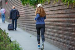 Young woman jogging along street in european city Royalty Free Stock Image