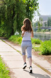 Young woman jogging alongside a river. Young woman jogging away from the camera along a pathway running alongside a river in a health and fitness concept Stock Images