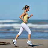 Young woman jogging on the beach Royalty Free Stock Images