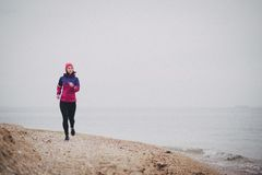Young woman jogging at the beach. Beautiful young woman wearing duffle jogging at the beach Royalty Free Stock Photos