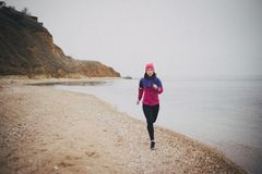 Young woman jogging at the beach. Beautiful young woman wearing duffle jogging at the beach Stock Images