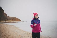 Young woman jogging at the beach. Beautiful young woman wearing duffle jogging at the beach Stock Image