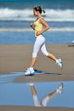 Young woman jogging on the beach Royalty Free Stock Photography