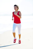 Young woman jogging on the beach in summer Stock Image