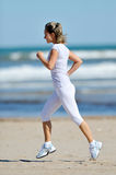 Young woman jogging on the beach in summer Royalty Free Stock Photo