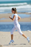Young woman jogging on the beach in summer Stock Photography