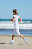 Young woman jogging on the beach in summer Stock Photos