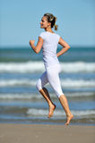 Young woman jogging on the beach in summer Stock Images