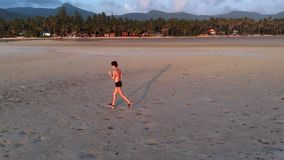 A young woman jogging at the beach on sunset. aerial drone shot, slow motion. A young woman with a slender figure jogging at the beach at sunset. She makes a run stock video footage