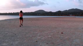 A young woman jogging at the beach on sunset. aerial drone shot, slow motion. A young woman with a slender figure jogging at the beach at sunset. She makes a run stock footage