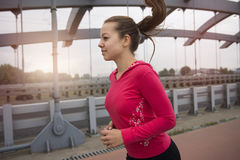 Young woman jogging on the bridge Royalty Free Stock Images