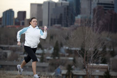 Young woman jogging in city. Young woman jogging in city park with downtown skyline in the background stock photos