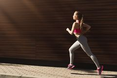 Young woman jogging in city copy space stock image