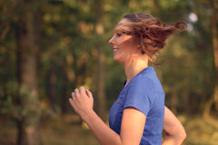 Young woman jogging in the countryside Stock Images