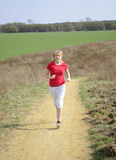 Young woman jogging on a dirt road Royalty Free Stock Photos