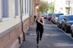 Young woman jogging down an urban street Stock Photo