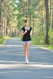 Young Woman Jogging in forest Stock Images