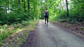 Young woman jogging through forest stock footage