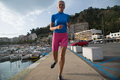 Young woman jogging in harbor in colorful sportwear Royalty Free Stock Image