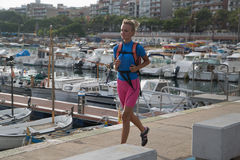 Young woman jogging in harbor in colorful sportwear Stock Photography