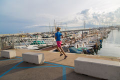 Young woman jogging in harbor in colorful sportwear Royalty Free Stock Images