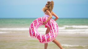 Young woman jogging with inflatable donut, with inflatable ring on the beach. Young woman jogging with inflatable donut, with inflatable ring on the beach stock footage