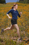 Young woman jogging through a meadow. Young woman jogging through a meadow of yellow flowers Stock Image