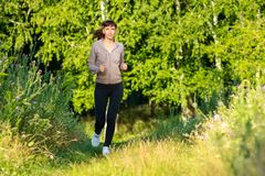 Young woman jogging in morning park Stock Photography