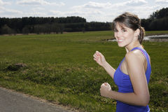 Young woman jogging outdoors Stock Images