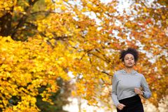 Young woman jogging outdoors in the park Stock Images
