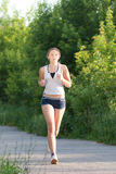 Young woman is jogging in the park Stock Images