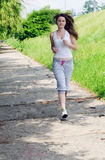 Young woman jogging through a park. Woman in casual clothes jogging a path through a park as she takes her daily exercise to keep fit Royalty Free Stock Images
