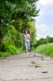 Young woman jogging through a park. Young woman  jogging along a path through a park as she takes her daily exercise to keep fit Royalty Free Stock Images
