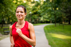 Young woman jogging in park. Healthy lifestyle - young beautiful woman jogging in nature stock photography