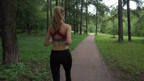 Young woman jogging in the park. Young woman jogging in a park stock video footage