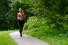 Young woman jogging in the park Royalty Free Stock Photos