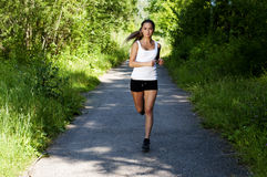 Young woman jogging in the park in summer. Trees and grass background Royalty Free Stock Photography