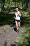 Young woman jogging in the park in summer Stock Photo