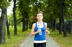 Young woman jogging in the park in summer Royalty Free Stock Photography