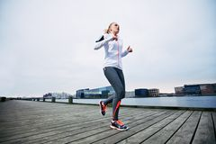 Young woman jogging by the river Royalty Free Stock Image