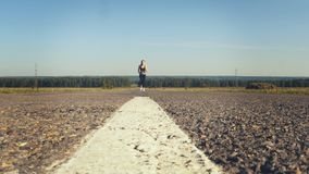Young woman jogging on the road. Low angle shot of adorable young woman jogging on the road on the morning stock footage