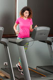 Young woman jogging on running machine in the gym Stock Images