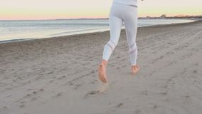 Young woman is jogging on the sand beach by the sea at sunrise in autumn, back view. Legs close-up. Young woman is jogging on the sand beach at sunrise in stock video