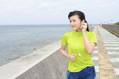 Young woman jogging by the sea Royalty Free Stock Photos
